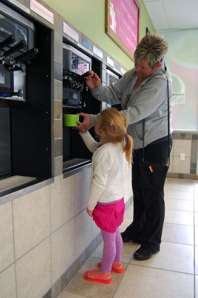 by: PHOTO BY: KYLIE WRAY - Before she moved on to the toppings, Evelyn chose vanilla frozen yogurt, helped by her grandmother, Debbie Cameron.