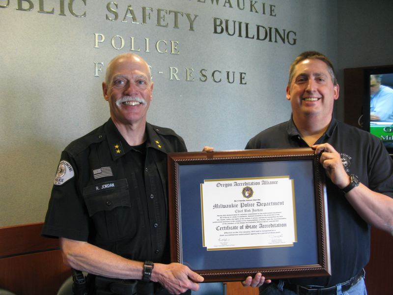 by: PHOTO BY: RAYMOND RENDLEMAN - Milwaukie Police Chief Bob Jordan and Lt. David Rash celebrate after last month's announcement that the department officially received state accreditation.