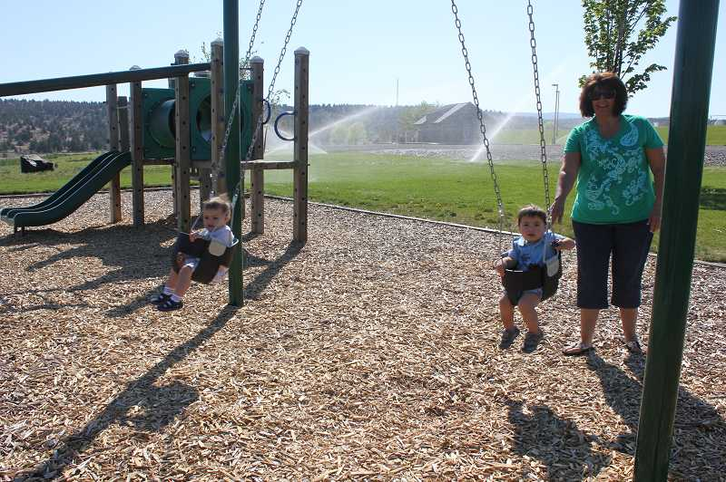 by: SUSAN MATHENY/THE PIONEER - Kriste Lofting pushes her grandkids, Berick Etter, left, and Liam Sando, both 1 1/2, on the new toddler swings at Juniper Hills Park.
