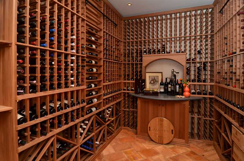 by: REVIEW, TIDINGS PHOTOS: VERN UYETAKE - The wine cellar has a 1,695-bottle capacity and is kept at 60â?° F. The floor is made of antique terra cotta Parefeuille tiles.