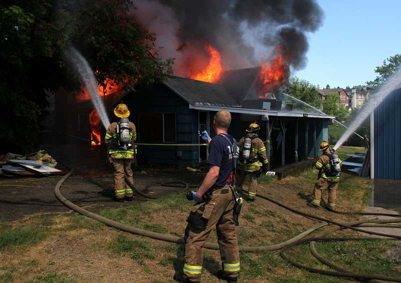 by: TIMES PHOTO: JONATHAN HOUSE - Tualatin Valley Fire & Rescue recruits gained valuable experience attacking a fire in a donated house.