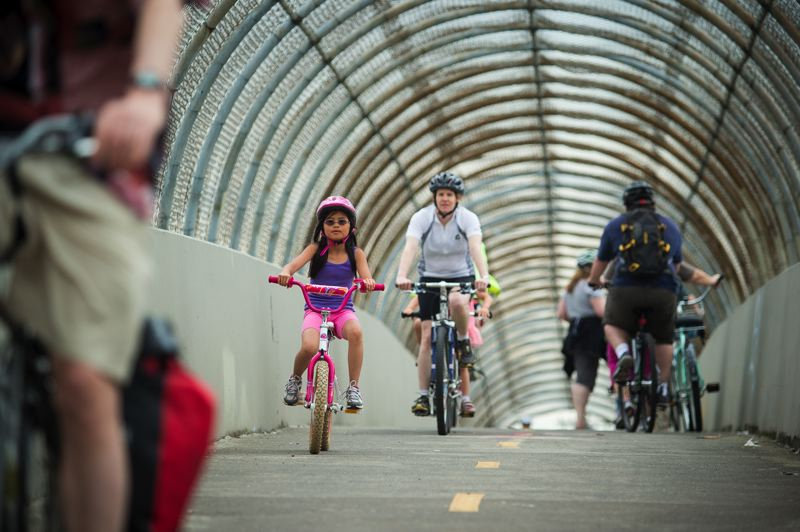 by: TRIBUNE PHOTO: CHRISTOPHER ONSTOTT - East Portland residents enjoy cruising along the Interstate 205 overpass and at Lents Park during Sunday Parkways kickoff event last week.