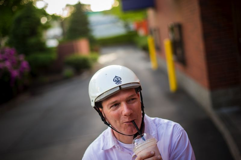 by: TRIBUNE PHOTO: CHRISTOPHER ONSTOTT - Houston Bolles sips his strawberry milkshake after ordering from the Burgerville drive-through window. Alas, no cup holder on his bike. More local stores are serving bike riders at drive up windows.