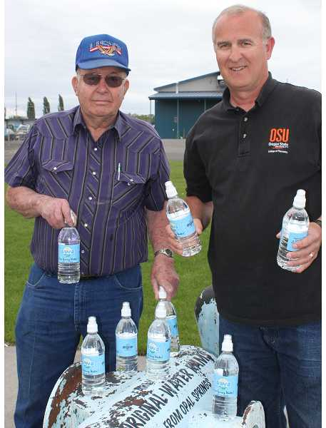 by: HOLLY M. GILL - Deschutes Valley Water District Chairman Eldon Barker, left, and Manager Ed Pugh, right, display bottles of the water that won best in state.