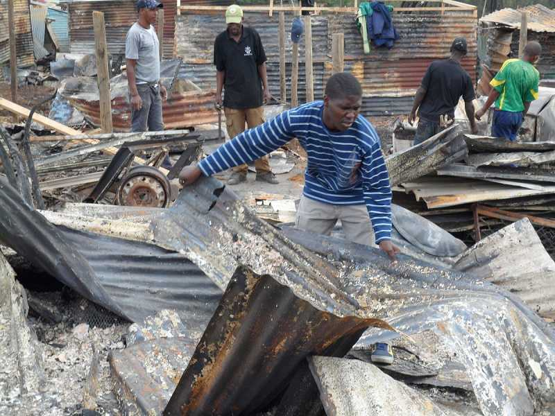 by: COURTESY OF PHUMLANI MTABE -  Phumlani Mtabe sifts through the rubble after a devestating fire destroyed his home and those of 4,500 villagers in Kayamandi, South Africa on March 14. An art show and concert will help students with the items they lost.