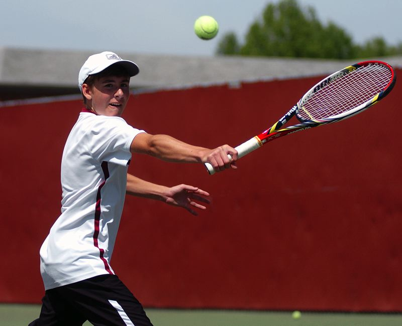 by: DAN BROOD - FAB FRESHMAN -- Tualatin freshman Ryan Malinowski hits a backhand shot during Saturday's third-place match at the Pacific Conference district tournament.