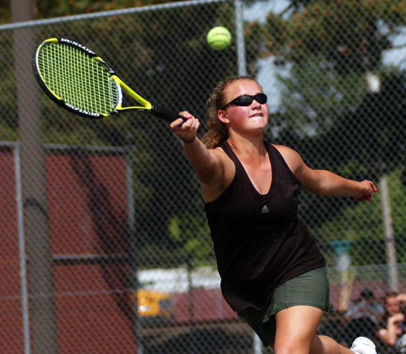 by: DAN BROOD - BIG EFFORT -- Tigard High School junior Courtney Roshak reaches for the during the girls doubles championship match Saturday at the Pacific Conference district tournament.