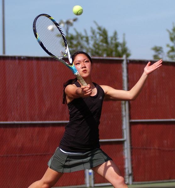 by: DAN BROOD - FOCUS -- Tigard sophomore Ayumi Mizuno keeps her eye on the ball during Saturday's district tournament doubles championship match.