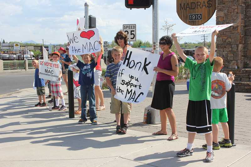 by: SUSAN MATHENY - Madras Aquatic Center supporters waved campaign signs last Friday at the U.S. Highway 26/97 intersection. The demonstraters were showing their support for the upcoming vote on an operation levy for the MAC Recreation District.