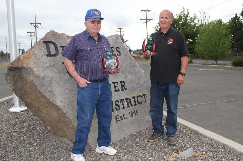 by: HOLLY M. GILL - Eldon Barker, chairman of the Deschutes County Water District Board of Directors, and Ed Pugh, manager of the district, hold the statewide trophies the district won recently for best over water in the state and best groundwater.