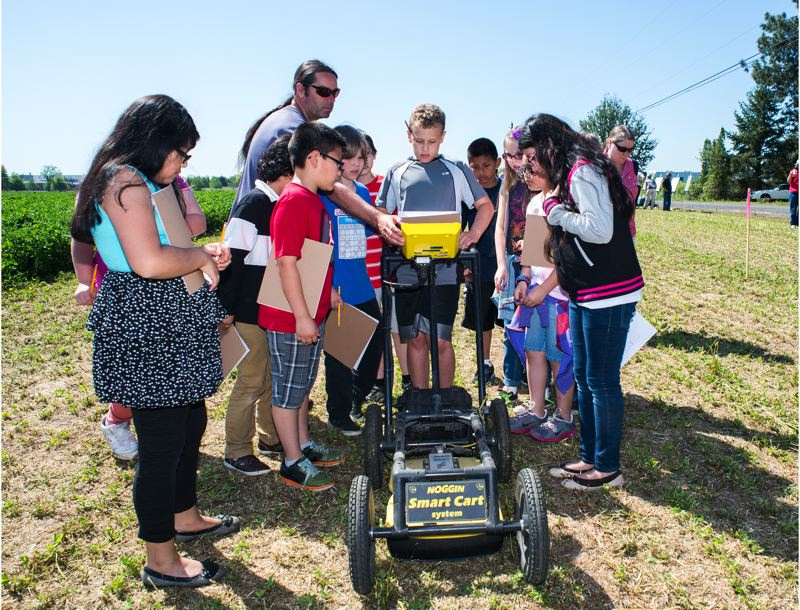 by: HILLSBORO TRIBUNE PHOTO: CHASE ALLGOOD - While at the road construction site on 253rd Avenue in Hillsboro, archaeologist Shawn Steinmetz, who works with the Confederated Tribes of the Umatilla Indian Reservations Pendleton-based Cultural Resources Protection Program, shows fourth-grade students from Tobias Elementary School how to use ground-penetrating radar to search for buried human remains.