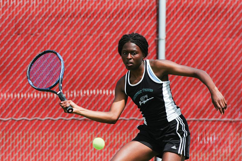 by: HILLSBORO TRIBUNE PHOTO: AMANDA MILES - Century sophomore Eka Essien prepares to hit a shot during her 6-1, 6-1 victory over younger sister Neyen Essien in the finals of the Pacific Conference district tennis tournament.