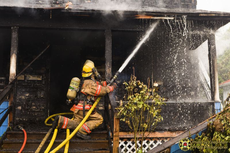 by: PORTLAND FIRE $ RESCUE/GREG MUHR - Firefighters battle a large house fire at 9005 N. Oswego Ave.