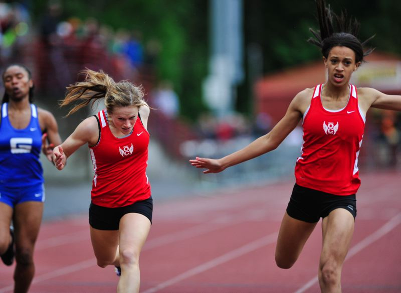 by: JOHN LARIVIERE - Oregon City juniors Karrin Shriner and Becca Houk on Friday proved themselves the class of the Three Rivers League in the sprints, going one-two in the 100 and 200. Above Shriner (right) wins the 200-meter dash in a school-record time of 25.52, finishing just ahead of Houk.