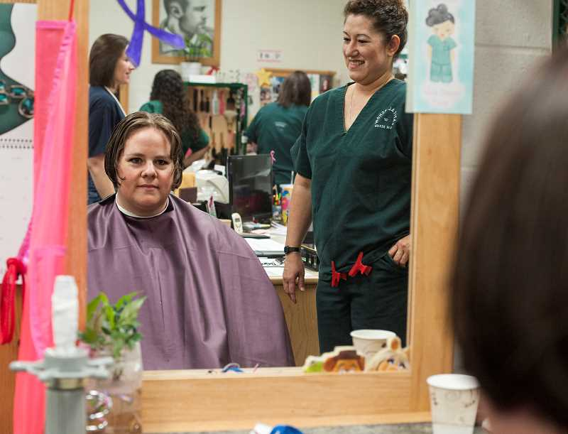 by: JOSH KULLA - Inmate Heather Jones, left, examines her newly trimmed hair, courtesy of inmate and cosmetology student Angela Kim, right.