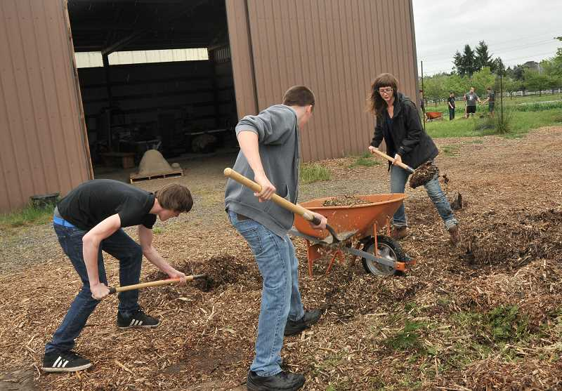 by: VERN UYETAKE - Holly Markham shovels mulch with Wilsonville students Dillon LeRuy, left, and Brent Self.