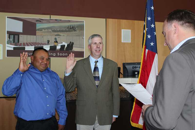 by: HOLLY M. GILL - Edgar Pineda and Jason Blackman are sworn in as Madras Police Department reserve officers by City Administrator Gus Burril on May 17.