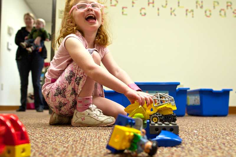by: TIMES PHOTO: JAIME VALDEZ - Sadie Pond, 4, of Beaverton, plays with Lego truck she built at Little Engineers, the Tigard business teaches students about engineering and robotics through LEGOS.