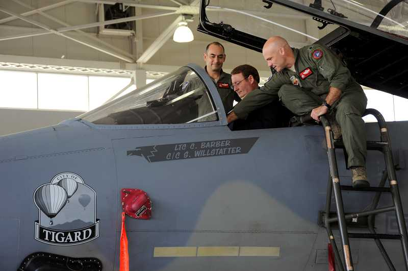 by: SUBMITTED PHOTO - Oregon Air National Guard Lt. Col. Christopher Barber, and Col. Matthew Schuster describe the instruments inside the F-15 Eagle to Tigard Mayor John L. Cook last week. An emblem bearing the citys name was christened on one of the 142nd Fighter Wings jets May 16.