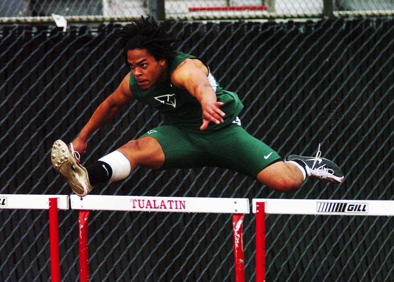 by: DAN BROOD - WINNING FORM -- Tigard High senior Zach Floyd is on his way to victory in the 110-meter high hurdles during the Pacific Conference district meet.