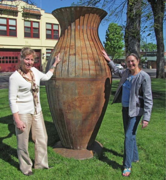 by: PHOTO BY ELLEN SPITALERI - Oregon City Library Director Maureen Cole, left, and Lynda Orzen, curator of the temporary sculpture garden, cozy up to 'Big Mouth.'