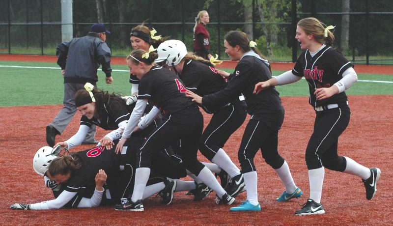 by: SANDY POST: PARKER LEE - Sandys Cheyenne Baker is mobbed by teammates after hitting the winning double in Fridays 3-2 playoff win over Redmond.