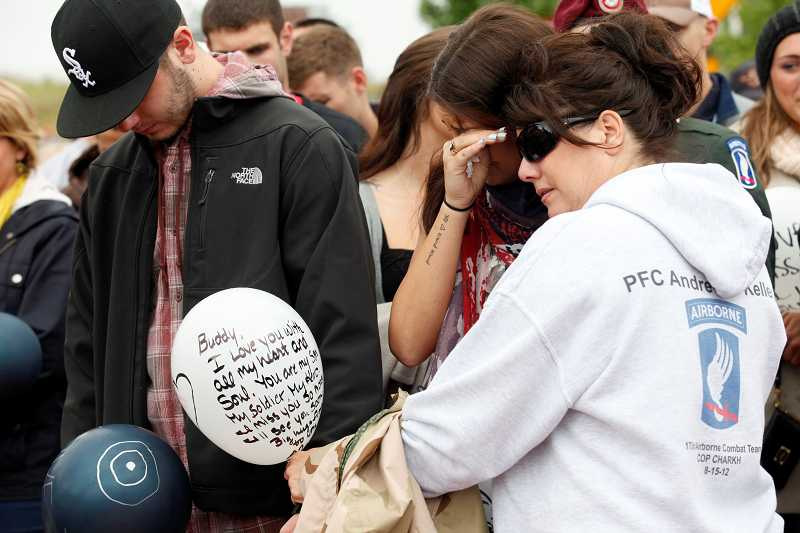 by: TIMES PHOTO: JONATHAN HOUSE - Derek Keller, Marissa Jones and Kim Keller cry as an American Flag is raised in Pfc. Andrew Keller's honor in the new Andrew Keller Memorial Circle on Southwest Barrows Road.