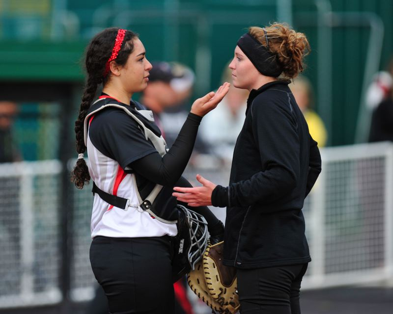 by: COURTESY OF JOHN LARIVIERE - Lincoln catcher Lexi Washington (left) confers on the mound with pitcher Courtney Huston as the Cardinals plot to stop a North Medford threat in the seventh inning.