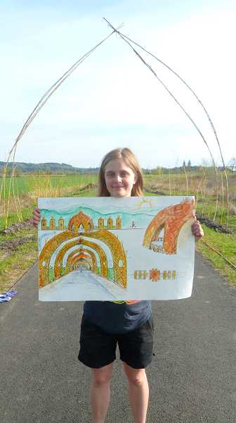 by: COURTESY PHOTO - Anna Lund stands near her willow villa holding a drawing by Robin Johnson, which predicts what the finished product will look like.
