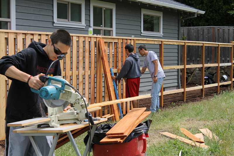 by: NEWS-TIMES PHOTO: JOHN SCHRAG - Dylan Hansen works on a fence on the north side of the 2013 Viking House.