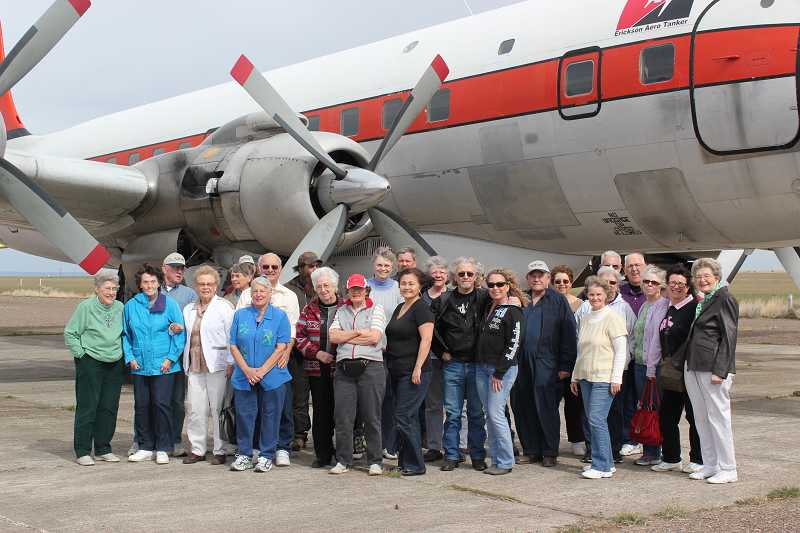 by: HOLLY M. GILL - Members of the On the Road Again Gang gather in front of one of Aero Tanker's DC-7s at the Madras Municipal Airport in March. About 30 members took part in that visit - one of the largest Gang groups ever.