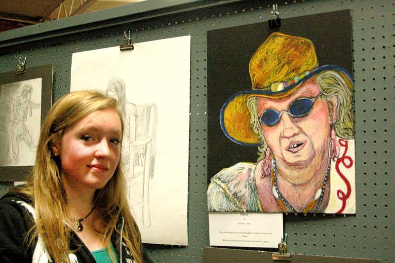 by: ISABEL GAUTSCHI - Eleventh-grader Desteny Lewis stands near her Spill inspired portrait. She won the art show's first-place prize for drawing.