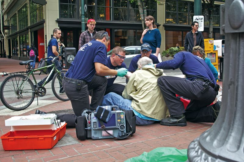 by: TRIBUNE PHOTO: JAIME VALDEZ - Portland Fire & Rescue firefighters Brady Donahue, Lt. Mike Wight, Sam Mulder and Monte Shirley assist a man who fell down on the sidewalk in front of Pioneer Place in downtown Portland.