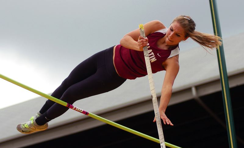by: DAN BROOD - VICTORIOUS VAULT -- Tualatin High School junior Laura Taylor clears the bar during the pole vault competition Friday at the Class 6A state track and field meet. Taylor took first place in the event with a height of 11-9.