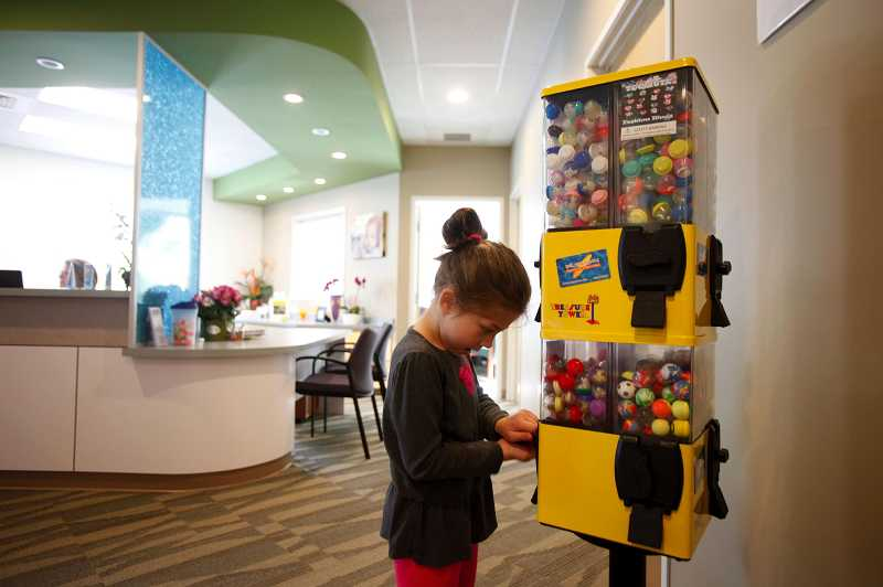 by: JONATHAN HOUSE - Persia Bowman inserts tokens into a toy machine at Kona Kids. Patients with good behaviour earn tokens during their visit to the dentist.