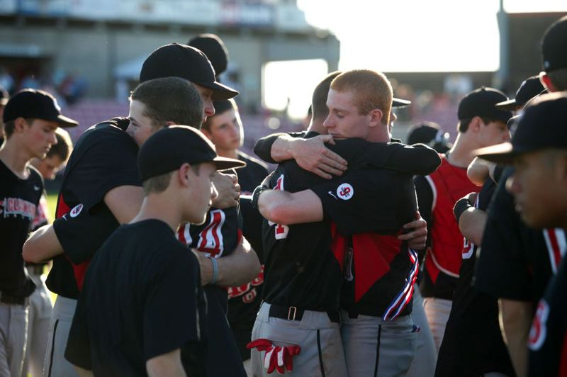 by: PAMPLIN MEDIA GROUP: JONATHAN HOUSE - Clackamas High baseball players console themselves after Saturday's 6-5 loss to Sheldon in the Class 6A championship game at Volcanoes Stadium in Keizer.