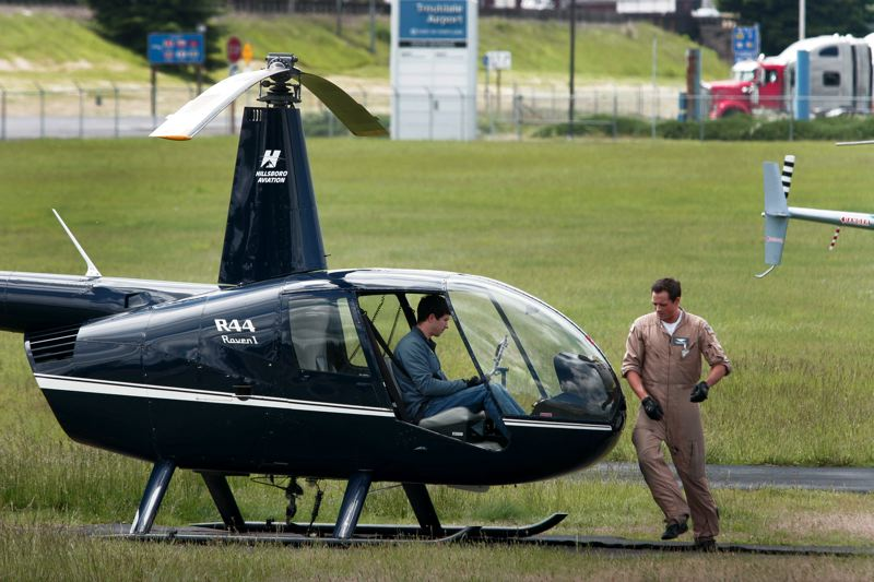 by: OUTLOOK PHOTO: JIM CLARK - Helicopter flight instructor Rusty Knudtson gets a student ready to fly at the Hillsboro Aviation flight school in Troutdale.