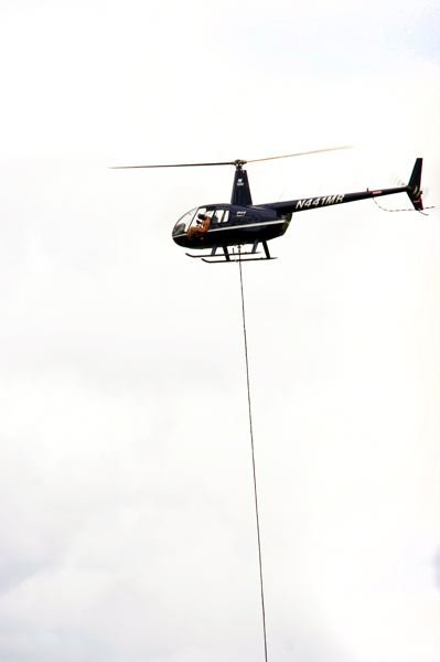by: OUTLOOK PHOTO: JIM CLARK - A helicopter pilot practices external load training, or how to maneuver equipment such as a water bucket to dump on fires, under the aircraft.
