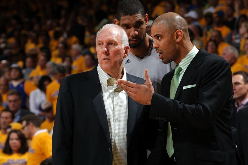 by: NBAE/GETTY IMAGES - Portland's Ime Udoka (right), first year assistant coach with the San Antonio Spurs, talks strategy with head coach Gregg Popovich (left) and All-Star big man Tim Duncan.
