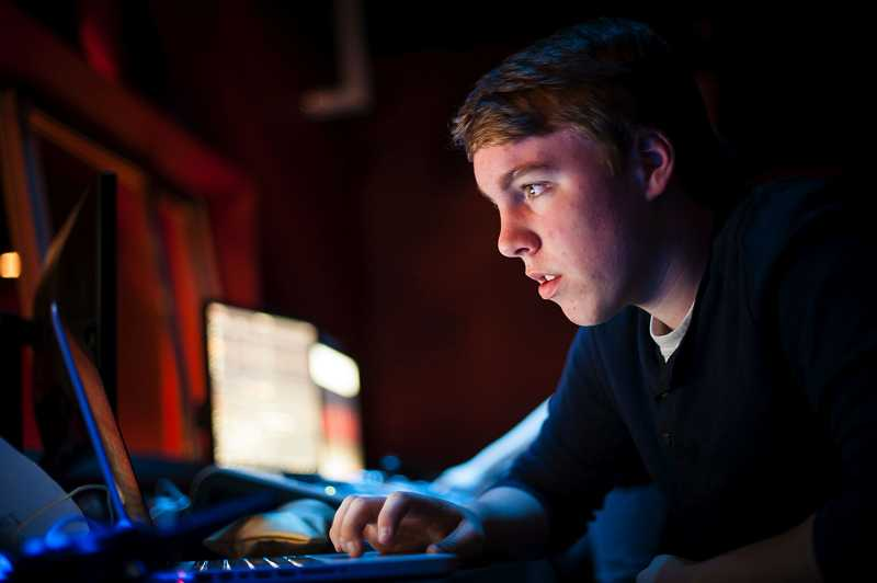 by: TIMES PHOTO: NICK FOCHTMAN - Sophomore Ryan Benson works in the lighting booth before the beginning of the big show.