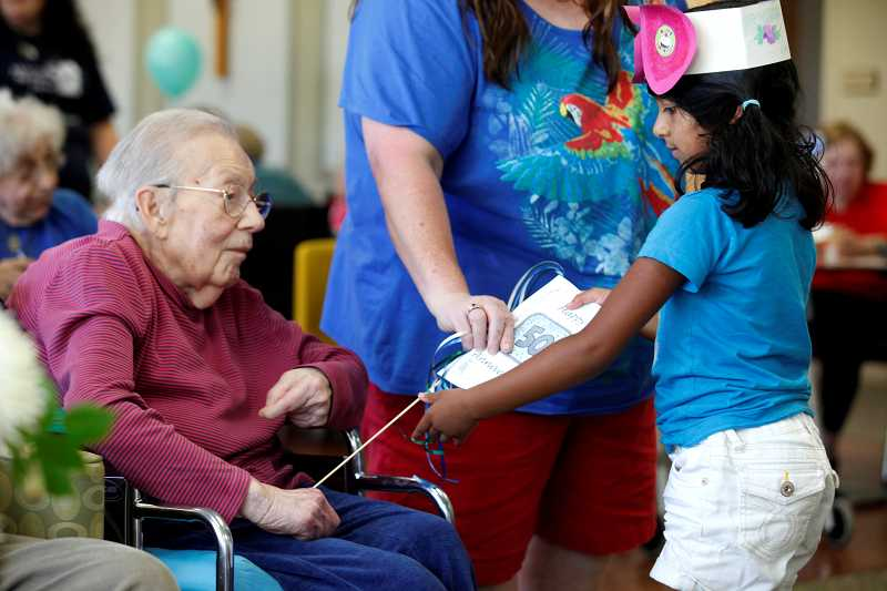 by: TIMES PHOTO: JONATHAN HOUSE - Sahana Srinivasan of the Valley Catholic Early Learning School gives a party favor to Maryville Nursing Home resident Connie Flabetich during a 50th anniversary celebration on Tuesday.