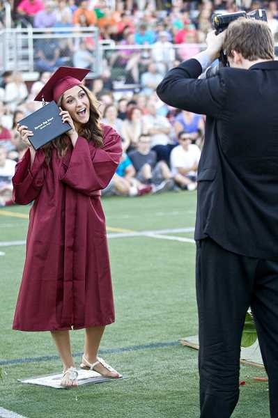 by: JAIME VALDEZ - Noelle Hebb poses for the cameraman with her diploma during Sherwood High School's graduation at Aaron J. Contreras Memorial Stadium.