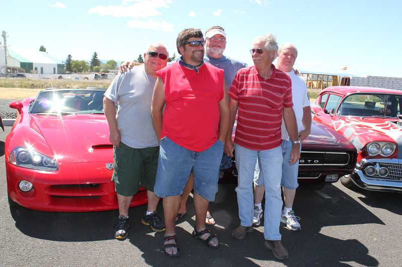 by: HOLLY M. GILL - From left, Tom Hansen, Brent Moschetti and Doug Lofting, who are in the process of organizing the car show portion of the 2013 Airshow of the Cascades, are joined by auto enthusiasts Bob Mammen, with his '58 Del Ray Chevy, and Gerald Tucker, with his '69 Pontiac GTO.
