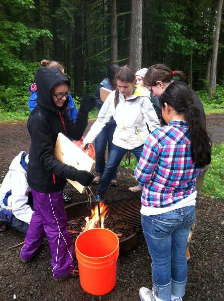 by: SUBMITTED - Gathering together to build a campfire are members of Lake Oswego Girl Scout Troop 45018. The girls won many top prizes at Camp Mountaindale.