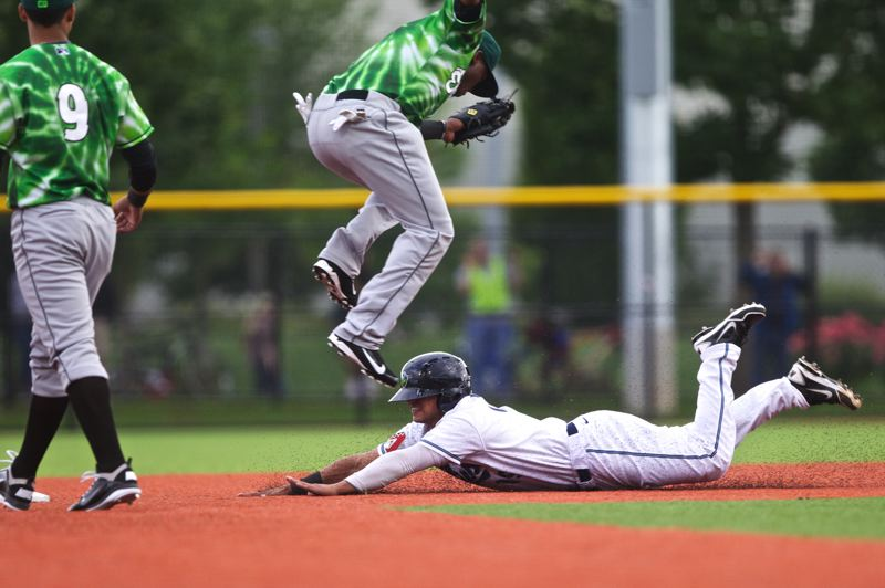 by: TRIBUNE PHOTO: JAIME VALDEZ - Yosbel Gutierrez of the Hillsboro Hops slides into second base under the feet of Eugene Emeralds second baseman Michael Bass. An announced crowd of 4,710 saw the Hops open their home season at Hillsboro Ballpark with a 12-0 win on Monday.
