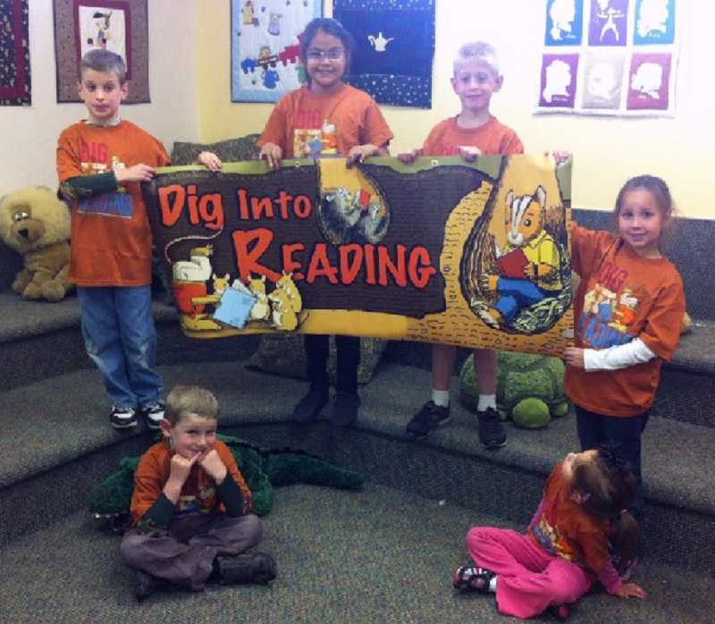 Kids hold a banner with this year's Summer Reading Program's theme.