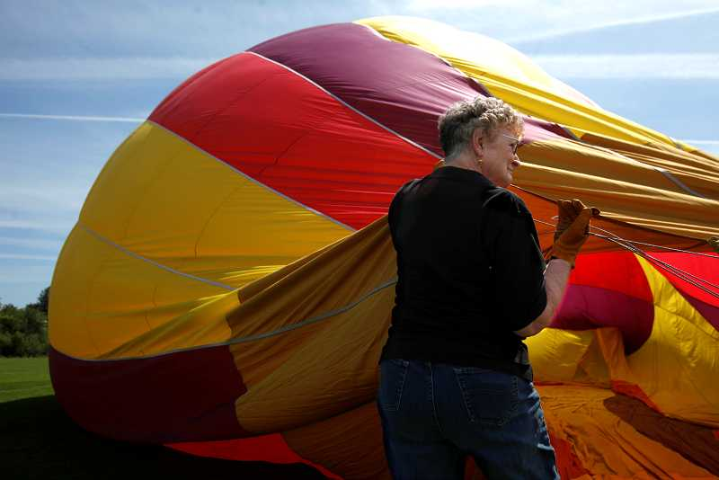 by: TIMES PHOTO: JONATHAN HOUSE - Mary Heath, a second-year volunteer, helps inflate the balloon Tierra Madre during a training session for Festival of Balloons volunteers. The Tigard event returns on Friday to Cook Park for three days of balloons, rides and music.