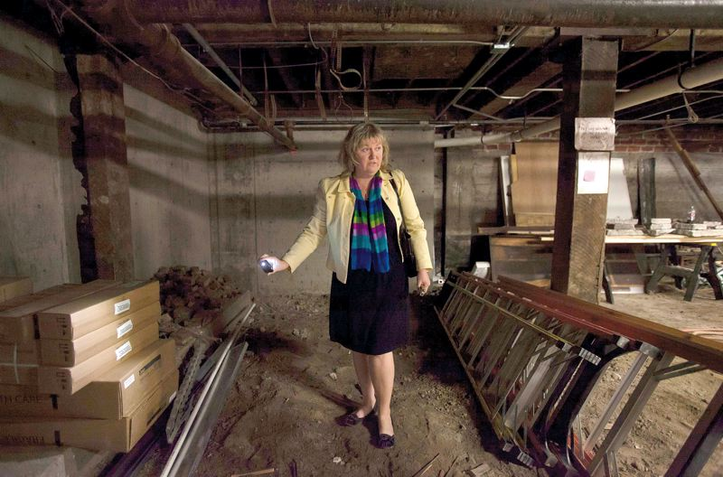 by: TRIBUNE PHOTO: JONATHAN HOUSE - Developer Julie Garver shows off the voluntary seismic upgrade that made possible redevelopment of the Rich Hotel in Old town. Concrete and bolts were used to stabilize the buildings walls.