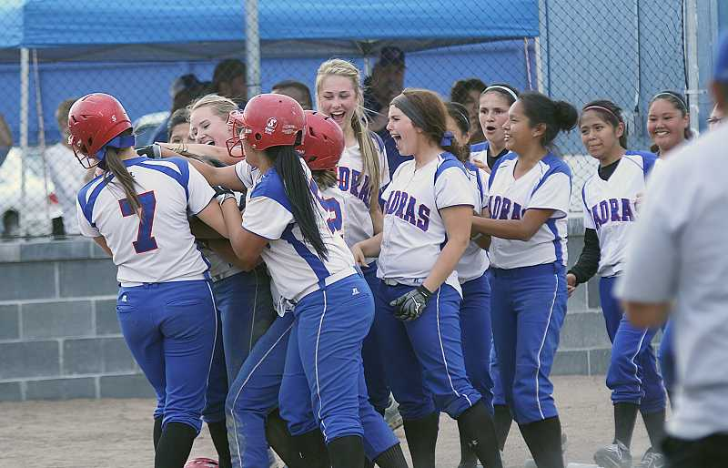 by: PIONEER FILE PHOTO - The Madras High School softball team, seen here tackling Sarah Brown following her walk-off three-run home run against North Marion in the last regular season game of the spring, made it to the Class 4A play-in round. They lost to North Marion, 13-1, to end their season.
