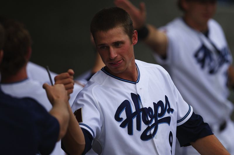 by: PAMPLIN MEDIA GROUP PHOTO: JAIME VALDEZ - Hillsboro's Josh Parr celebrates in the dugout after scoring the first run on Monday in the Hops' home opener at Hillsboro Ballpark.